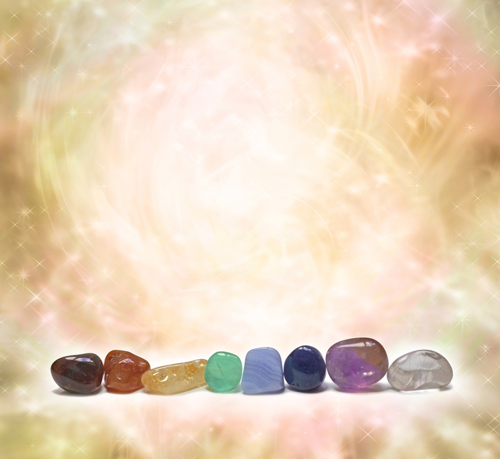 Chakra Crystals emitting beautiful energy -  a row of chakra colored tumbled semi precious gemstones on a swirling sparkling ethereal golden pastel colored background with plenty of copy space